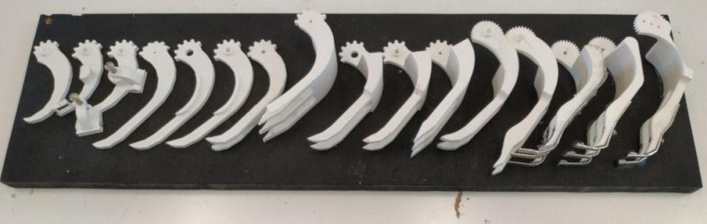 Les 14 versions imprimées en 3D d'une pince pour robot holonome. vidéo prototypage cooprint Fabrication designer créatif Prototype prototypage Paris ingénieur mécanique développement projet impression 3d cooprint